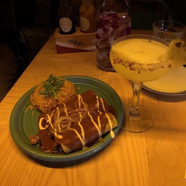 "A plate with two enchiladas drizzled with vegan ""cream"", and a cocktail with pineapple garnish."