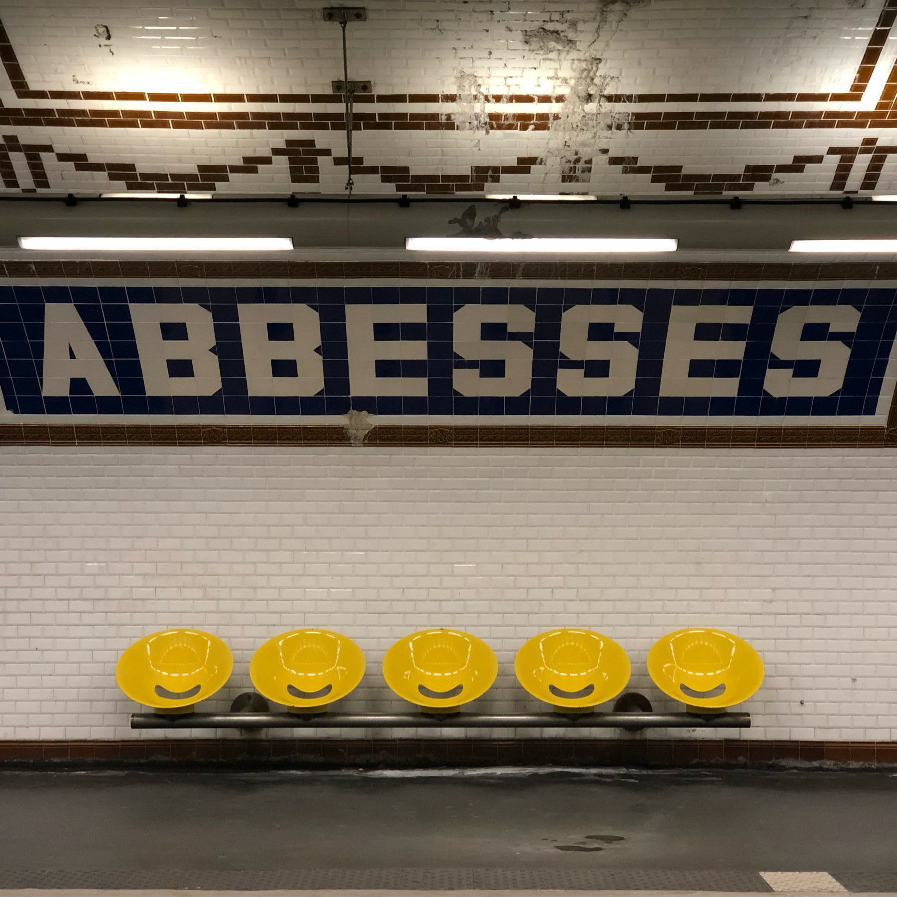 "Subway station wall with tile ""Abbesses"" lettering."