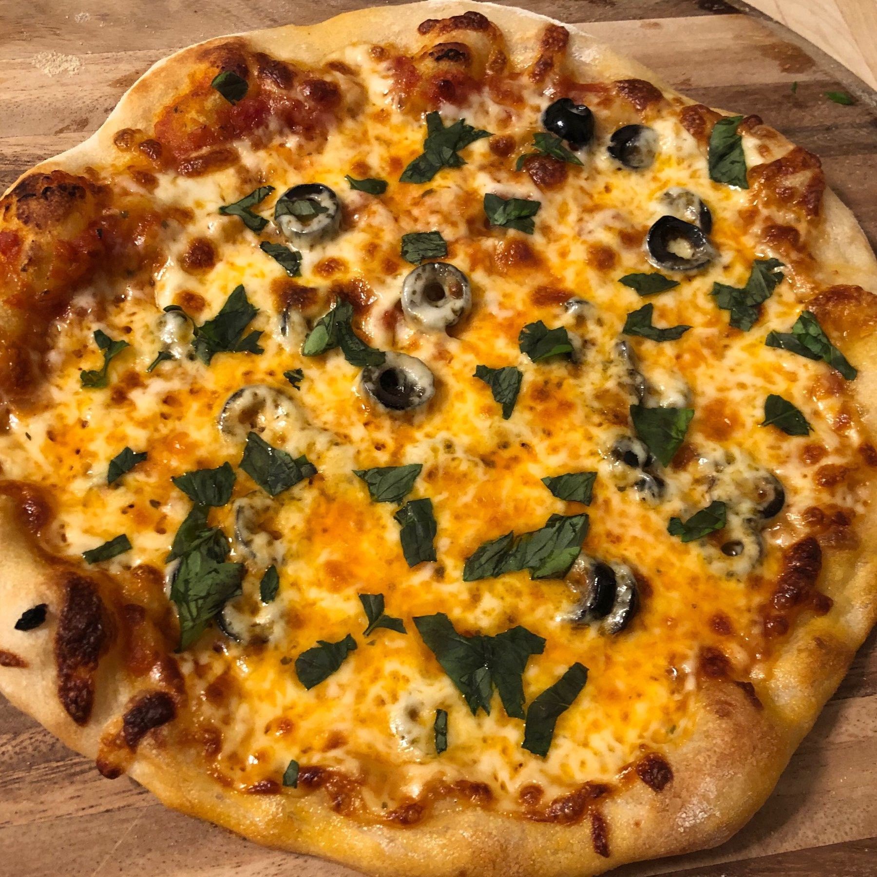 Fully baked pizza with olives and basil.