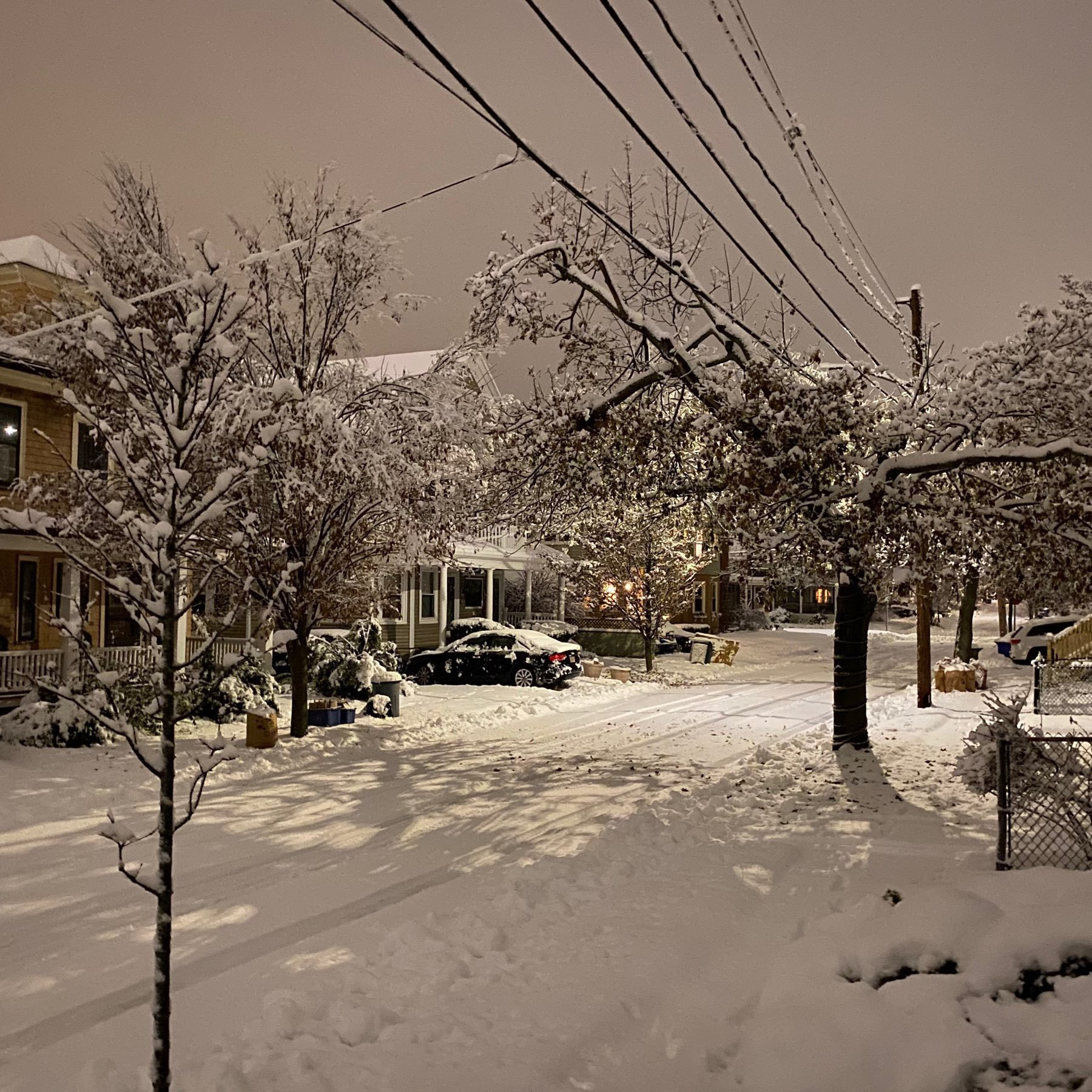 snow covered street with houses and powerlinea