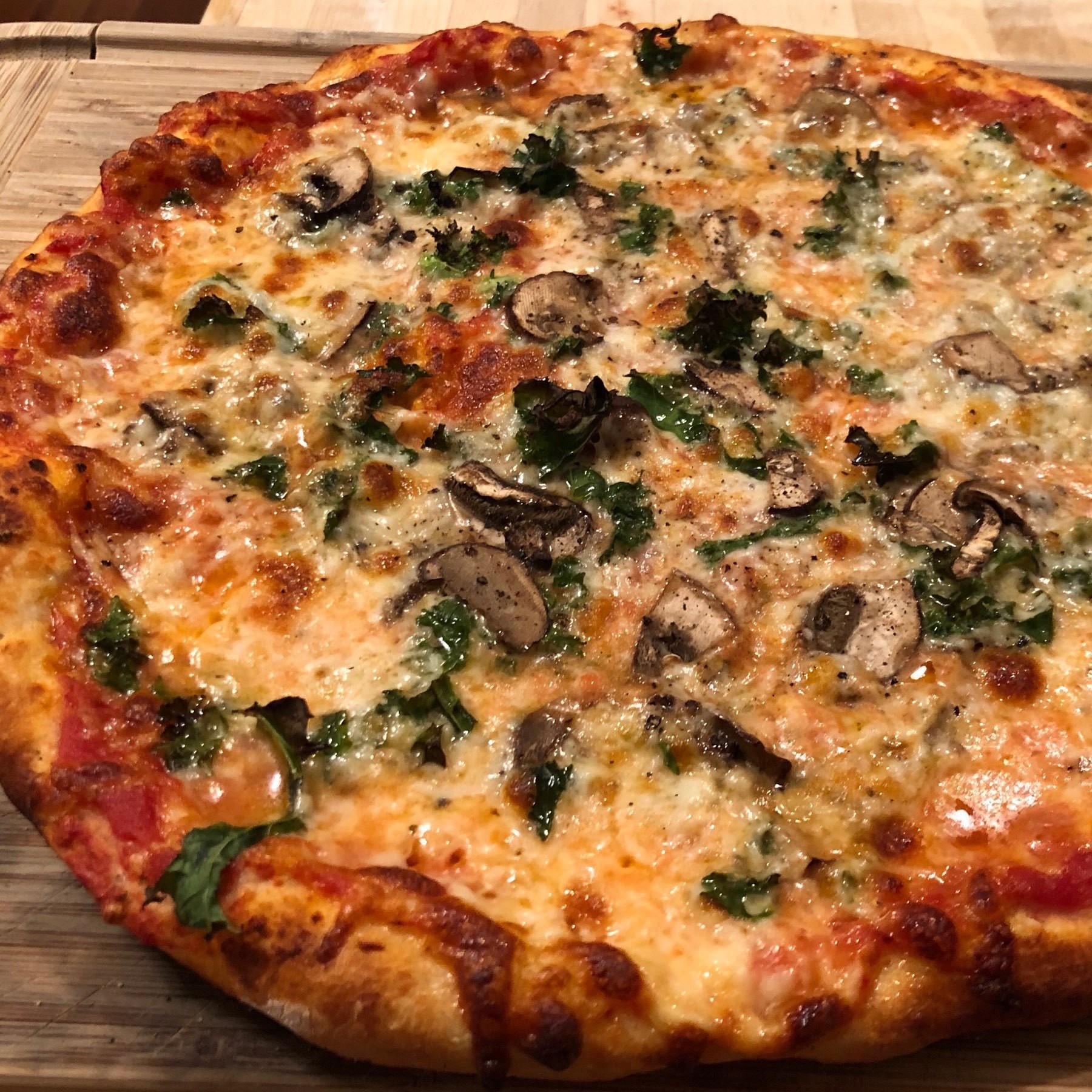 Close up on kale and mushroom pizza.