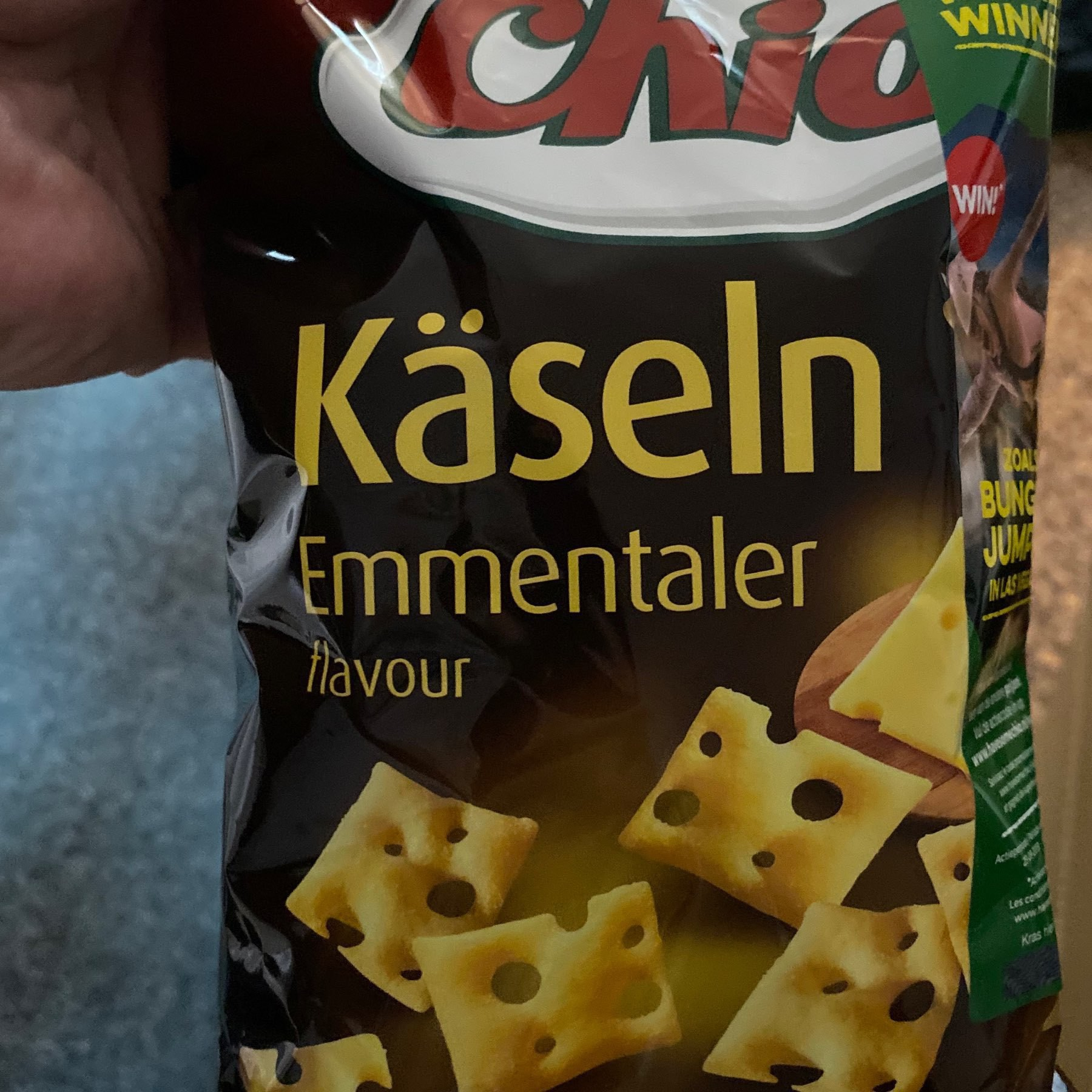 "Picture of a snack bag with ""Käselin Emmentaller"" descriotion and crackers with swiss-cheese wtule holes."