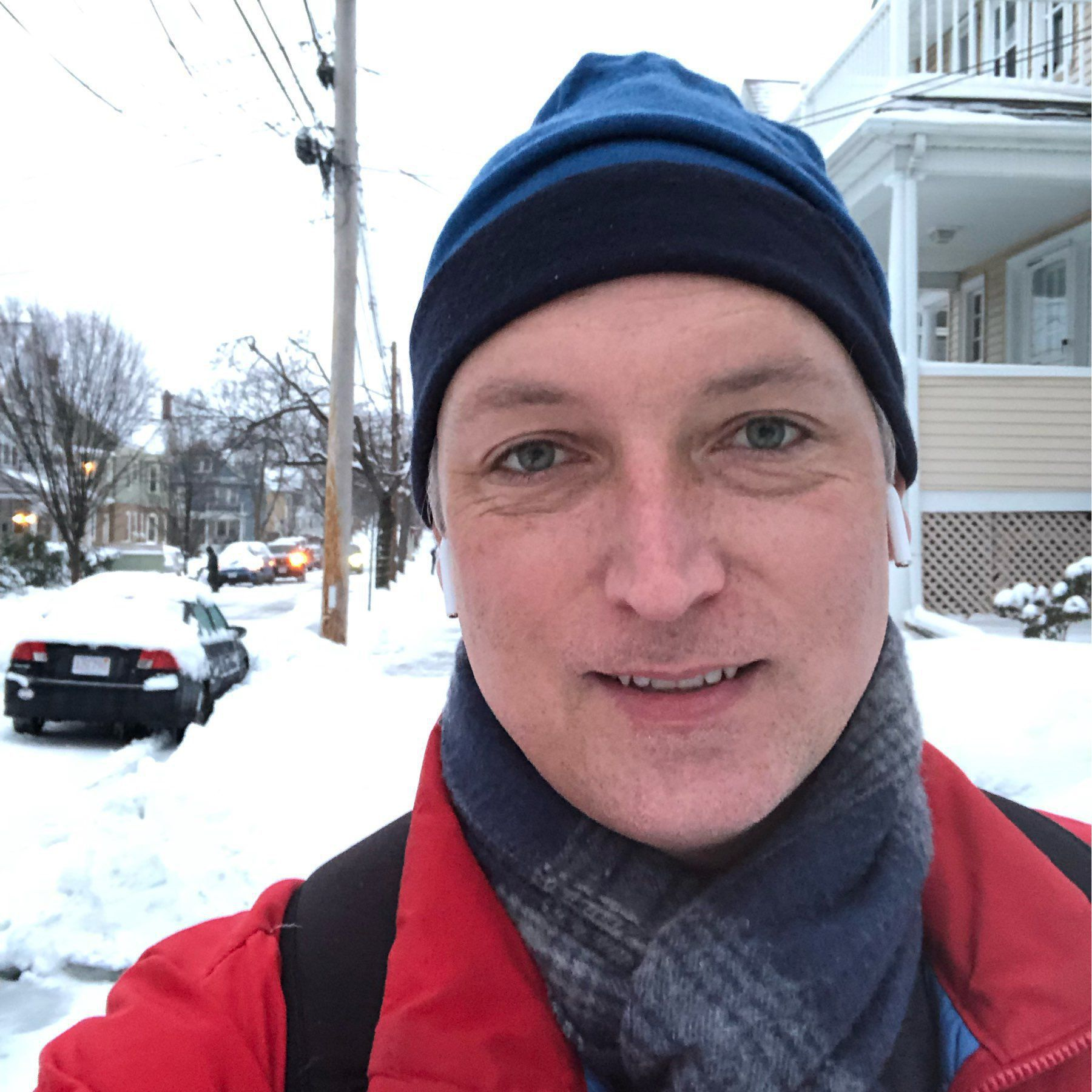 Self portrait against a backdrop of snow covered street, cars, and houses.