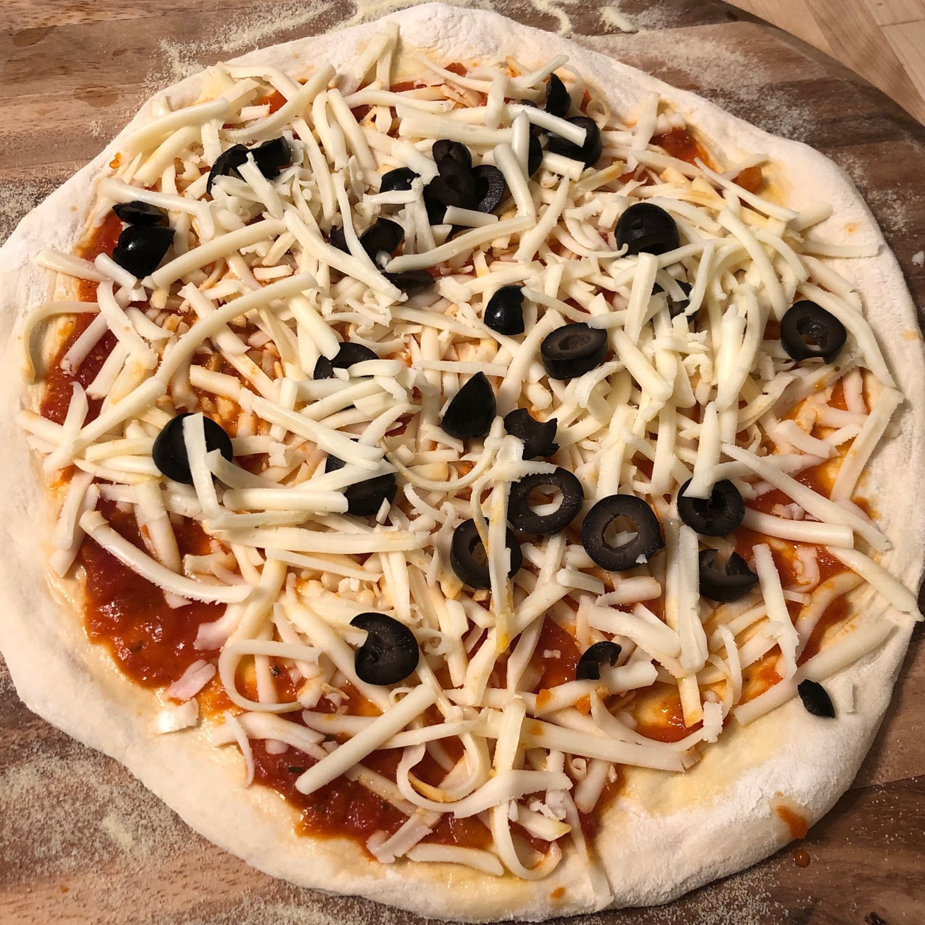 Raw pizza with grated mozzarella and black olives.