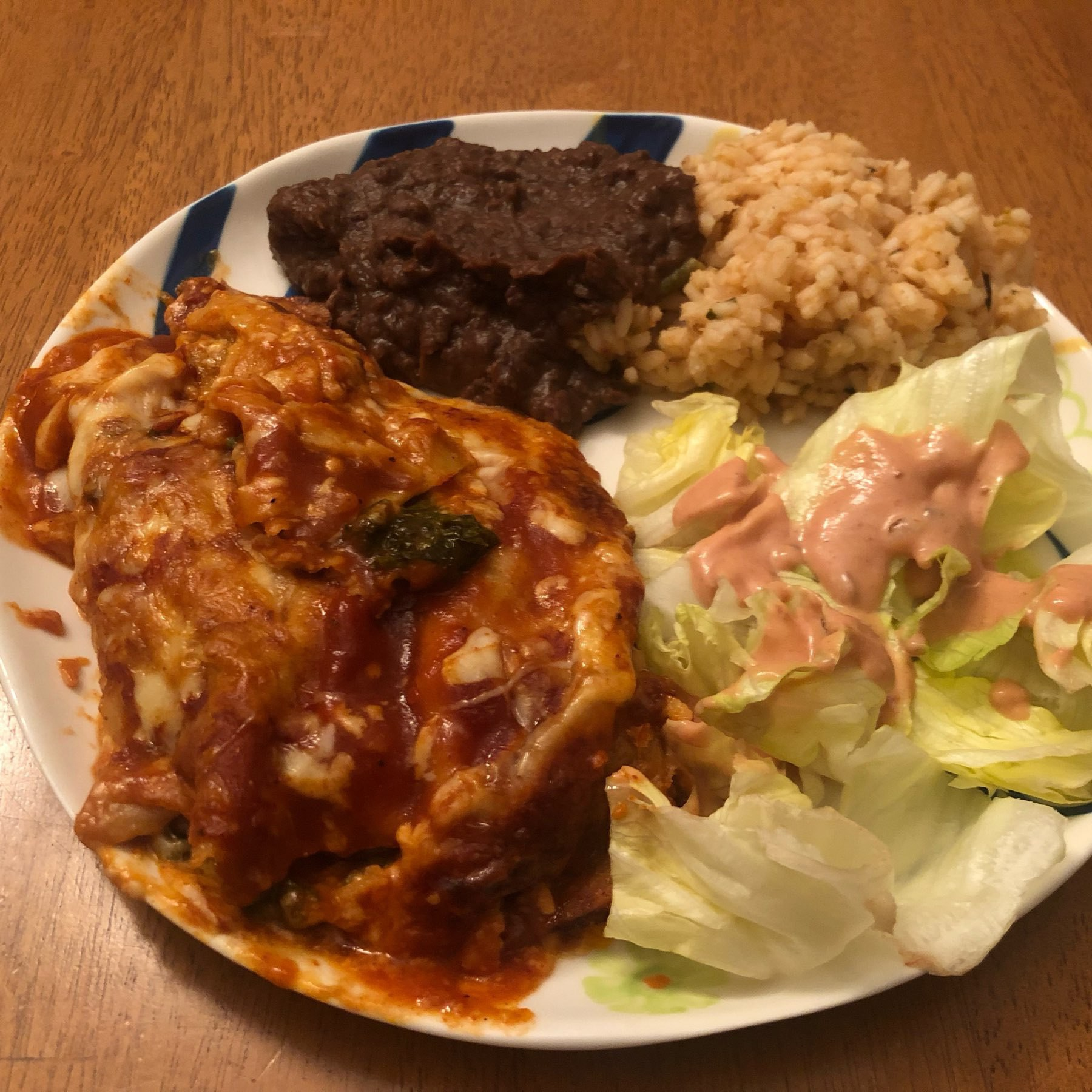 Homemade enchiladas with rice, beans, iceberg salad.