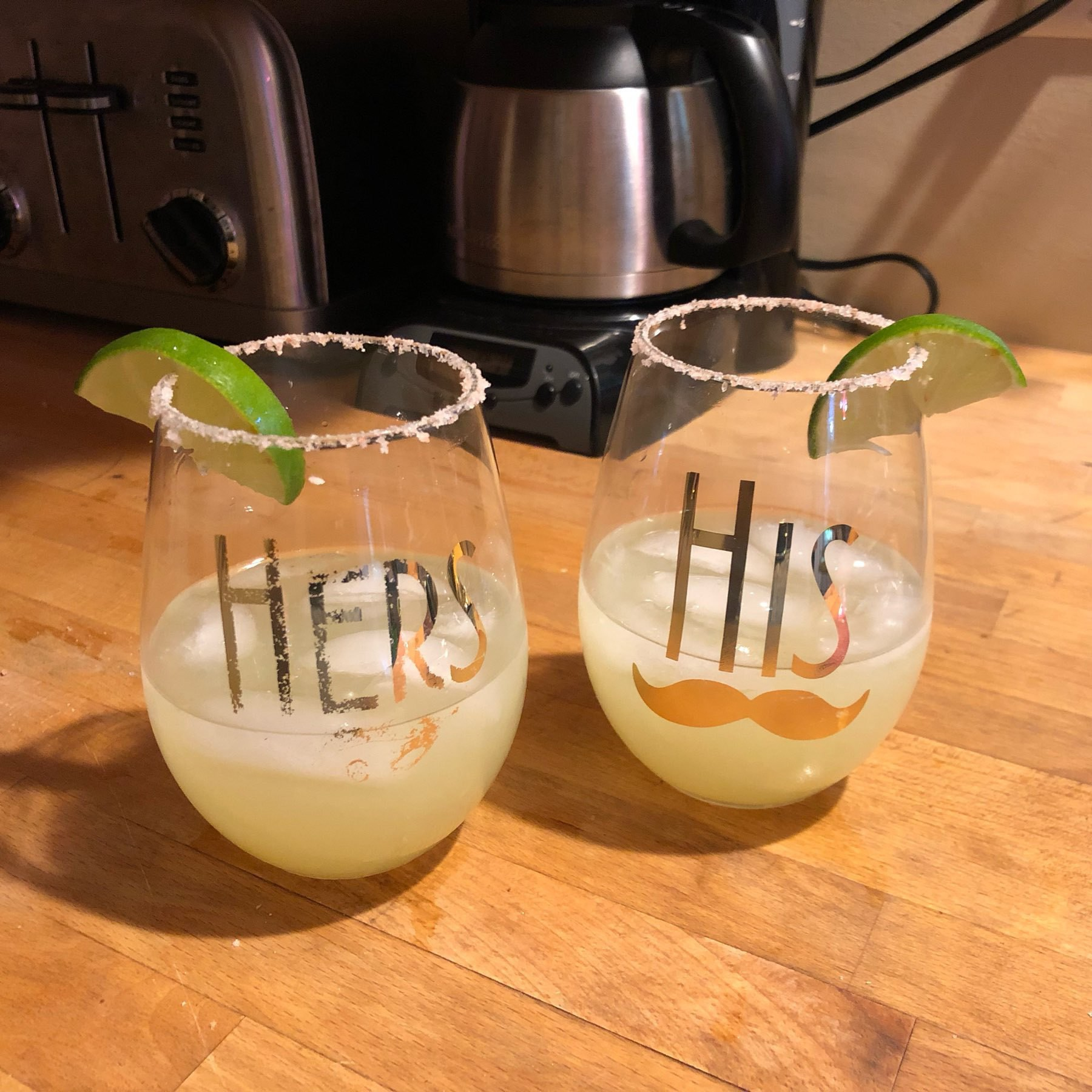 "Stemless wine glasses, embossed with gold ""His"" and ""Hers"" decals, partly filled with ice and margarita cocktails."