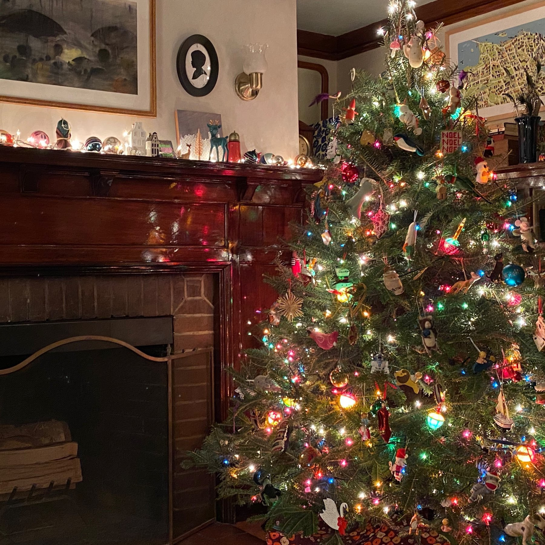 Brightly lit christmas tree against backdrop of fireplace with lights and stockings.
