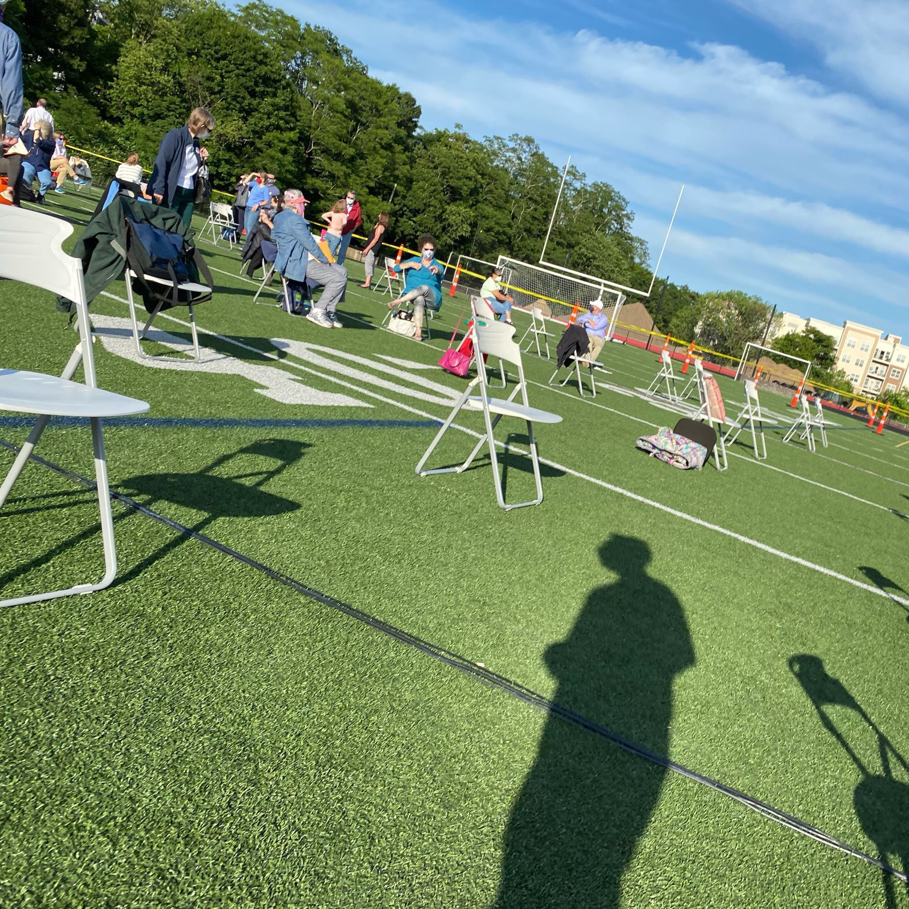Shot of chairs spaced widely on a football field