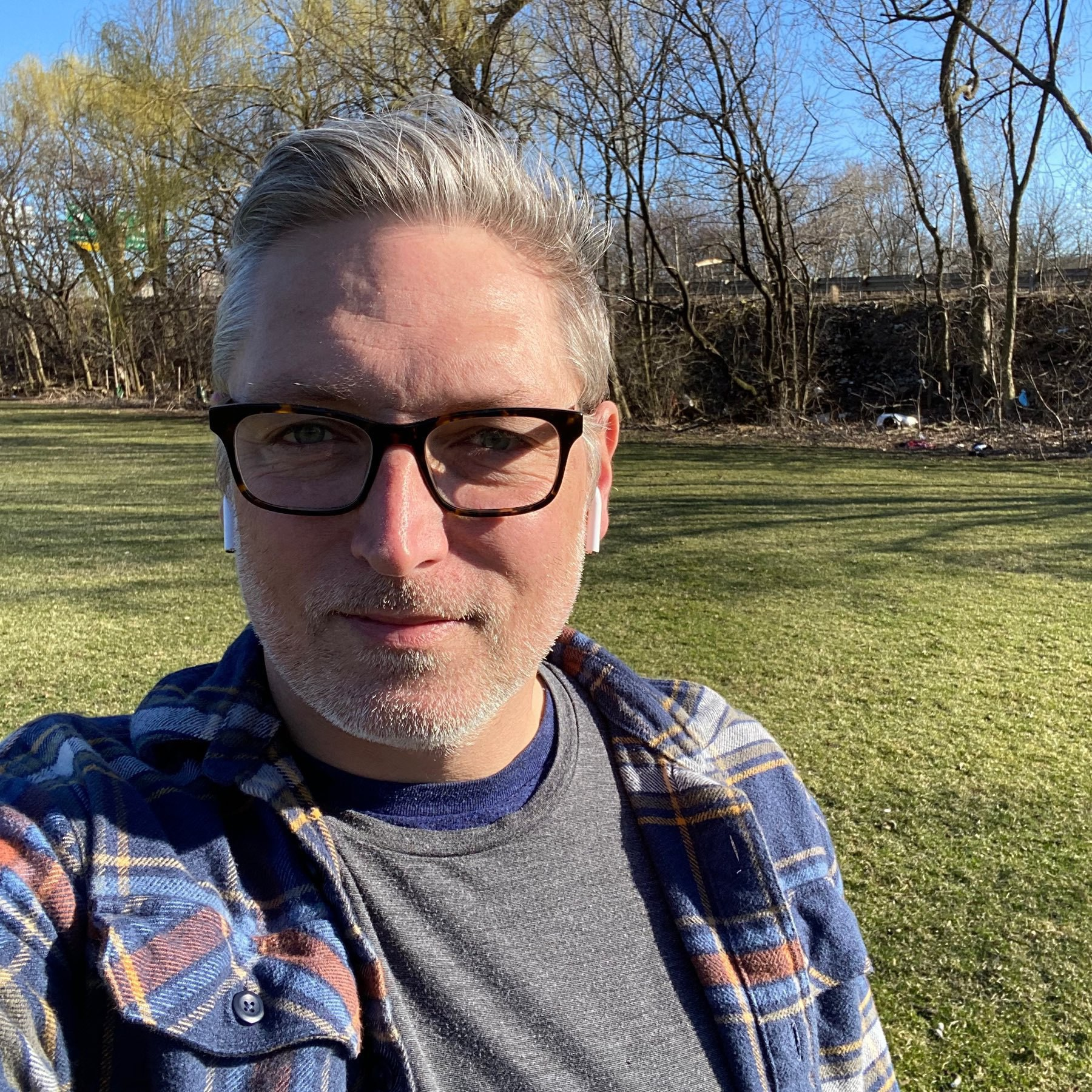 Self portrait against backdrop of green grass and trees.