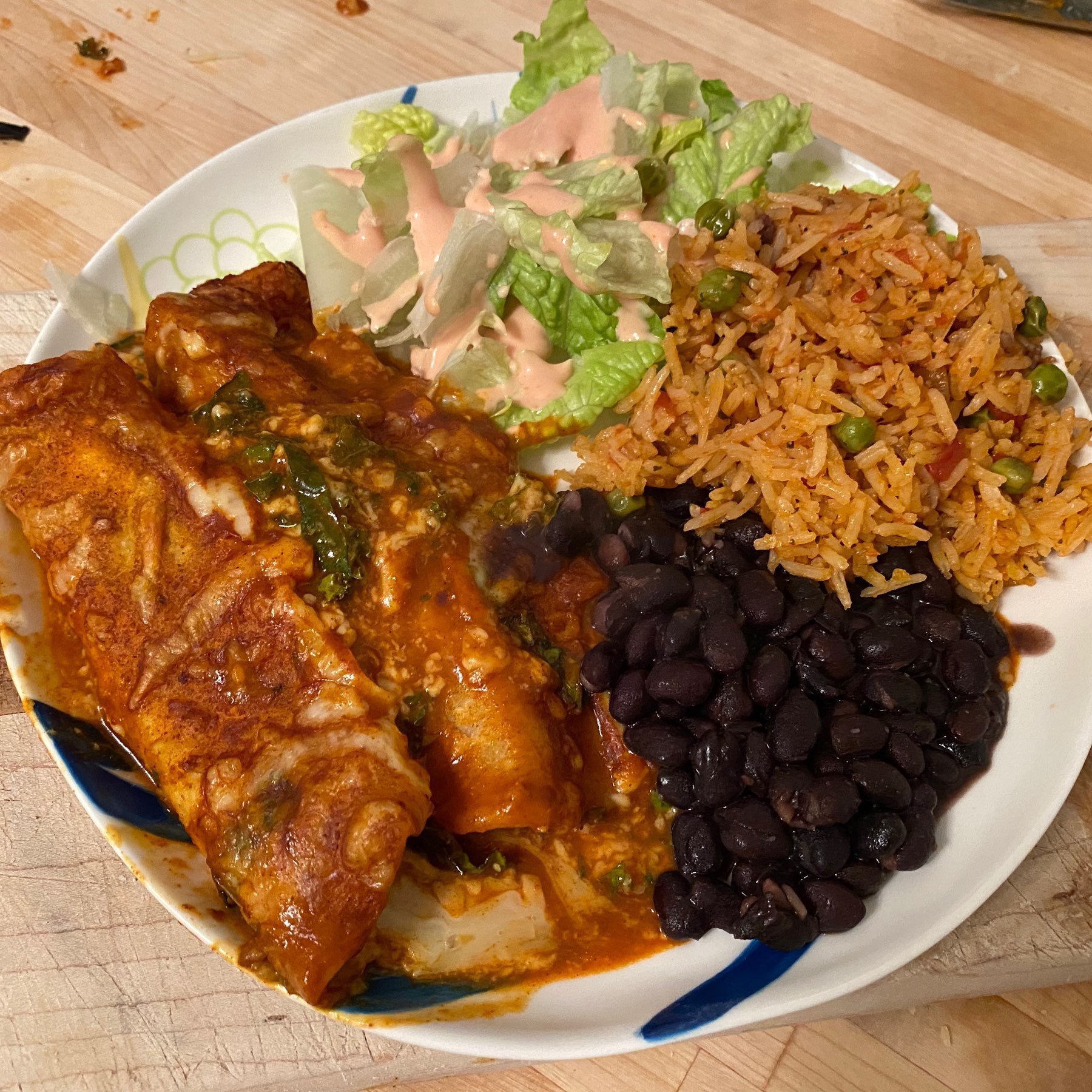 plate with kale enchiladas, beans and rice
