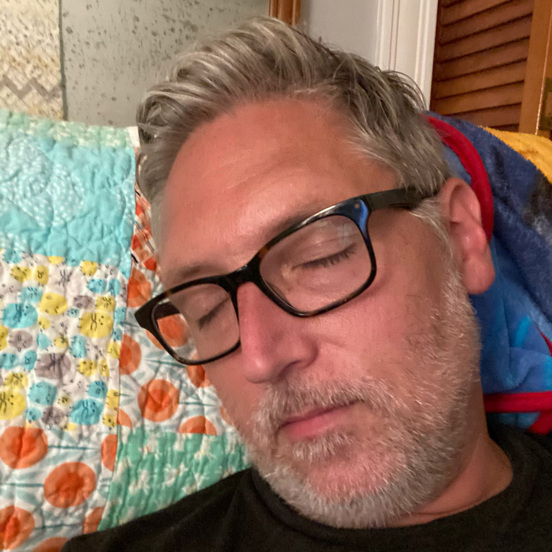 self portrait feigning sleep in a quilted chair