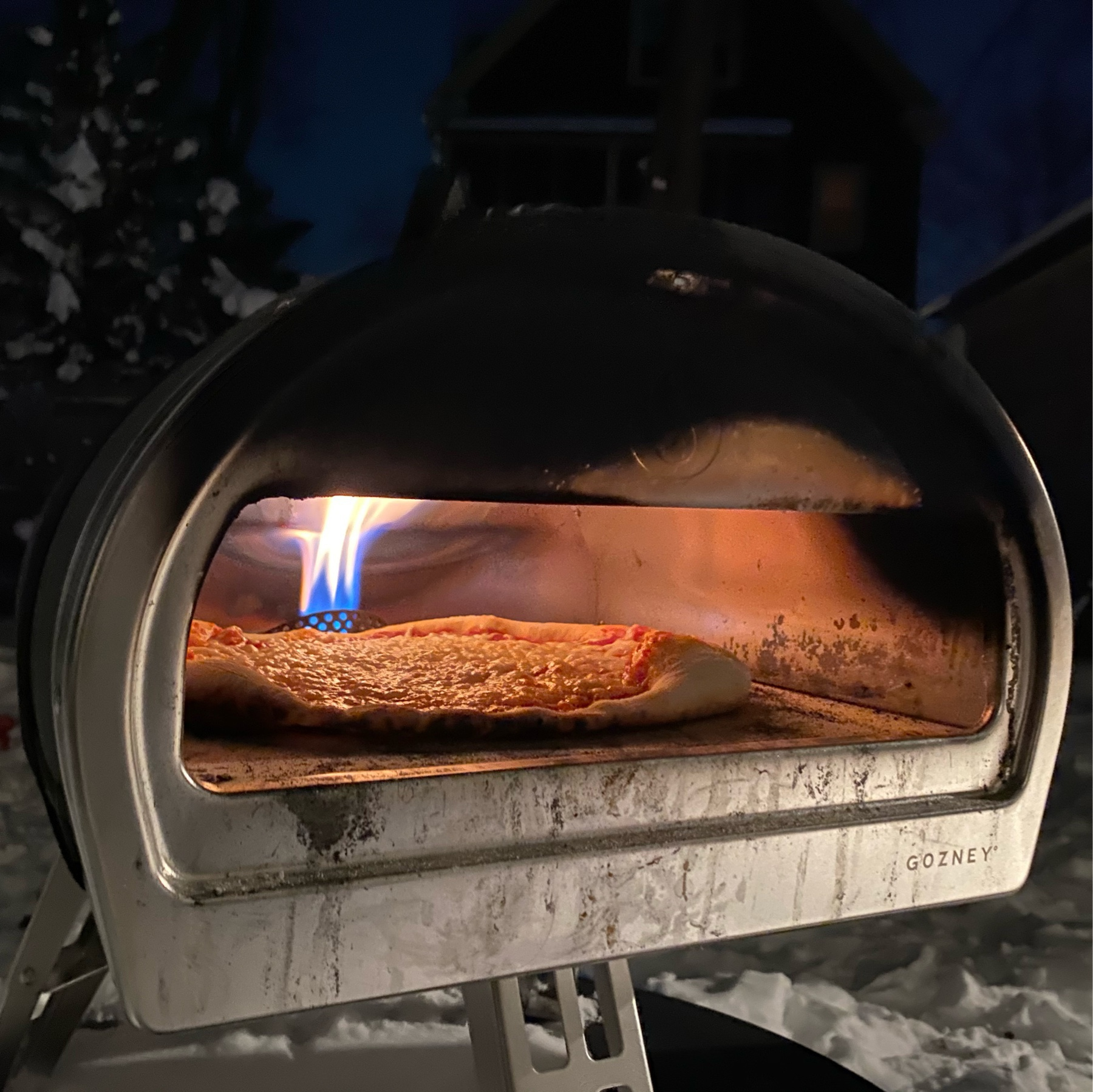 picture of a pizza oven with flame glaring against a backdrop of snow