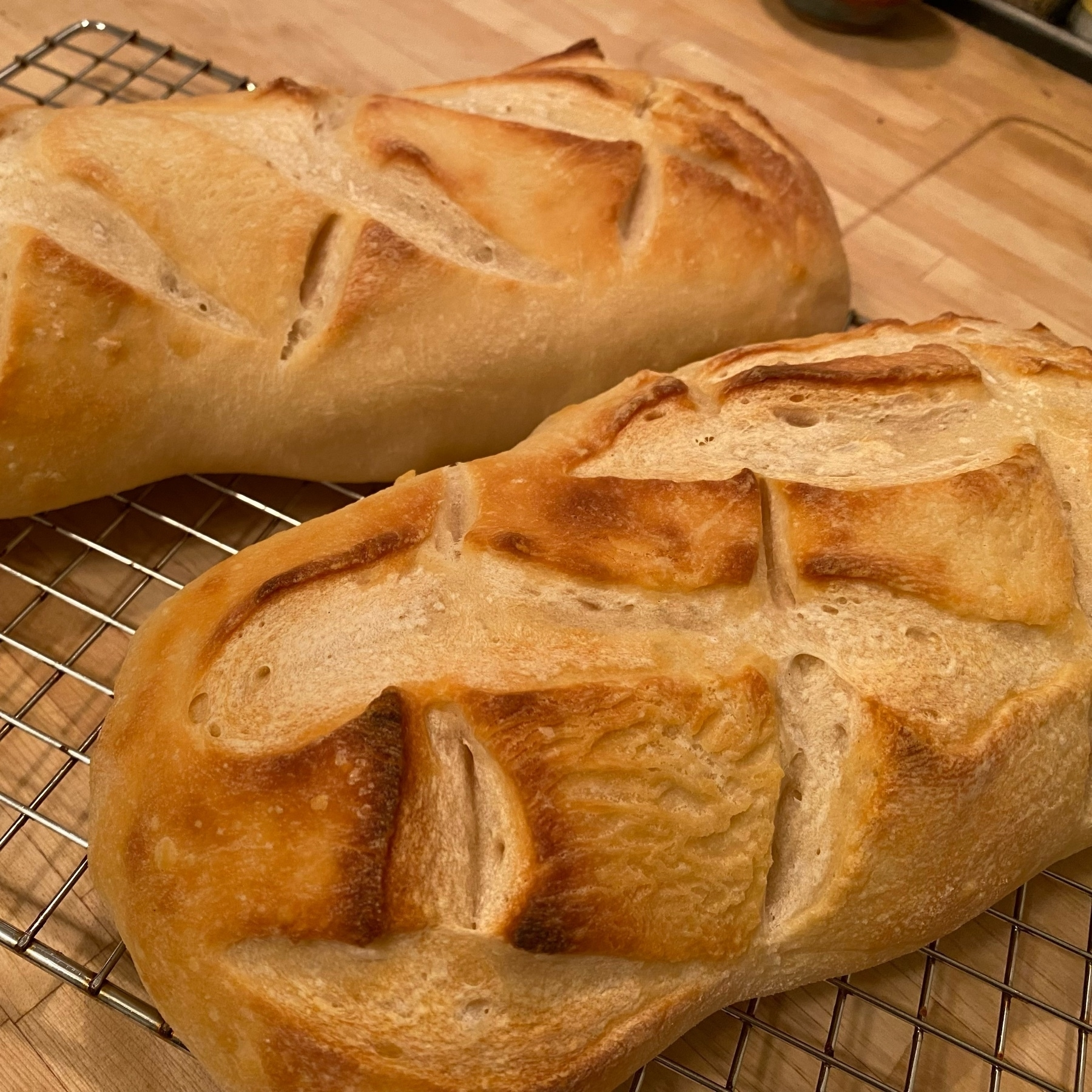 picture of two loa es of freshly baked bread with criss-cross slash patterns on top