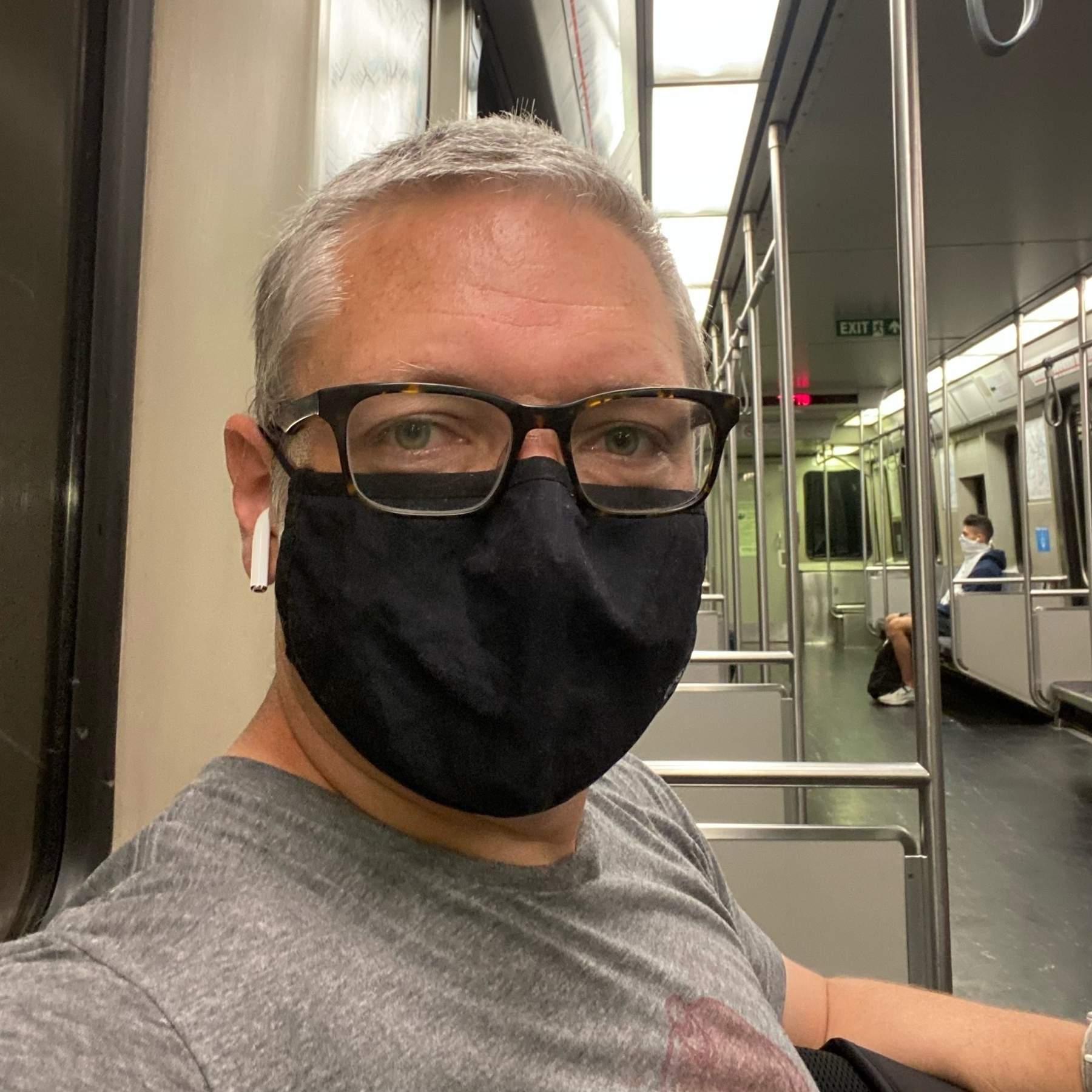 selfie wearing a black facemask on an almost empty subway car