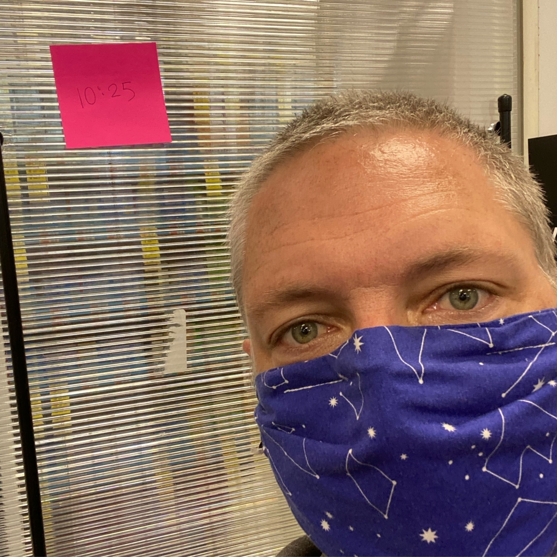 """Self portrait wearing a constellation mask, beside a post-it note """"10:25"""" in a pharmacy waiting area."""