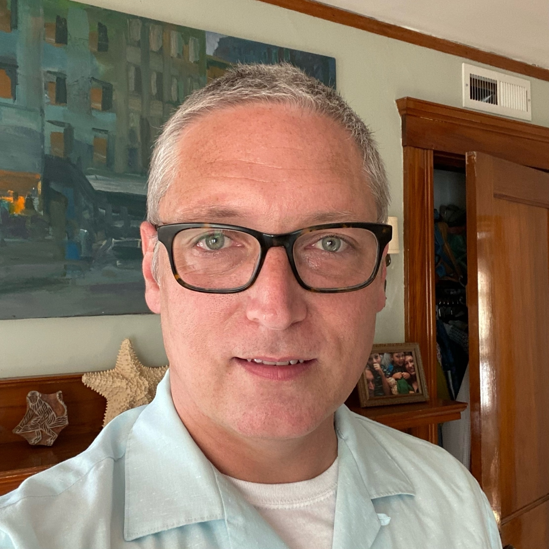 self portrait clean shaven with short greying hair, glasses, and a vintage button-up shirt
