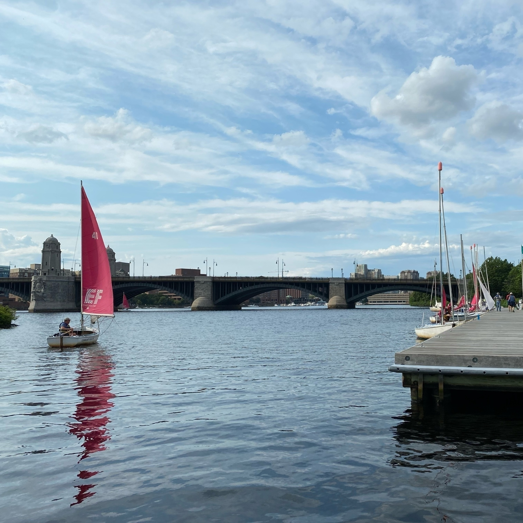 A sailboat on the Charles river with Longfellow Bridge in the background.