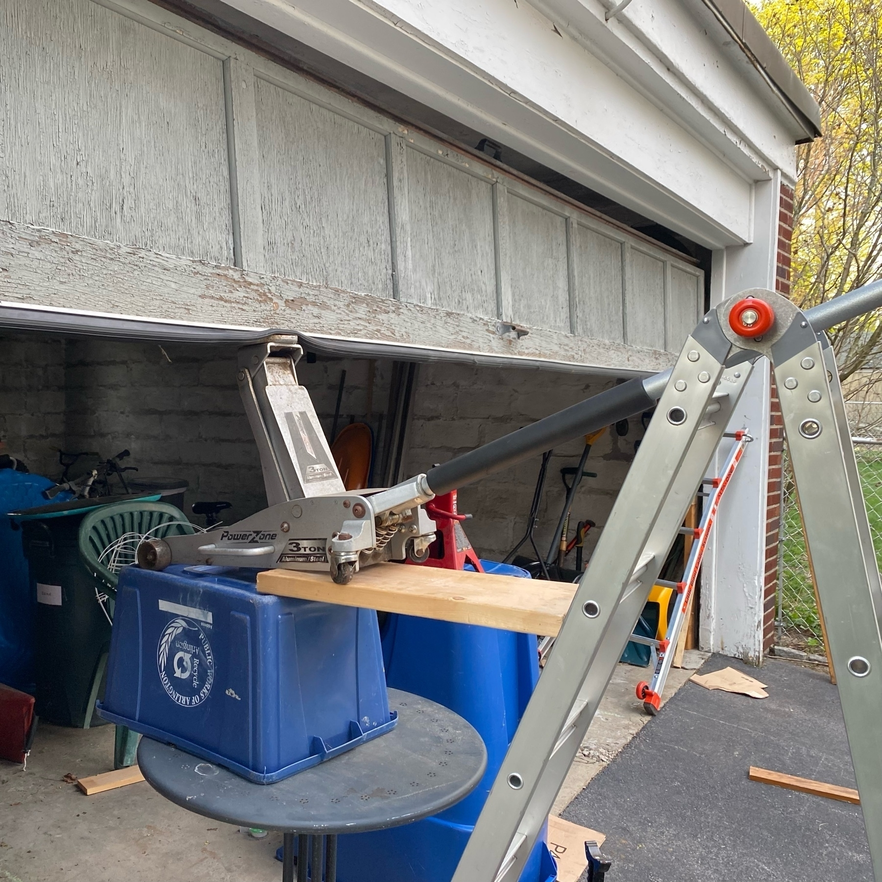 pictue of a garage door being held open by a contrived combination of table, recyling bin, and automotive floor jack