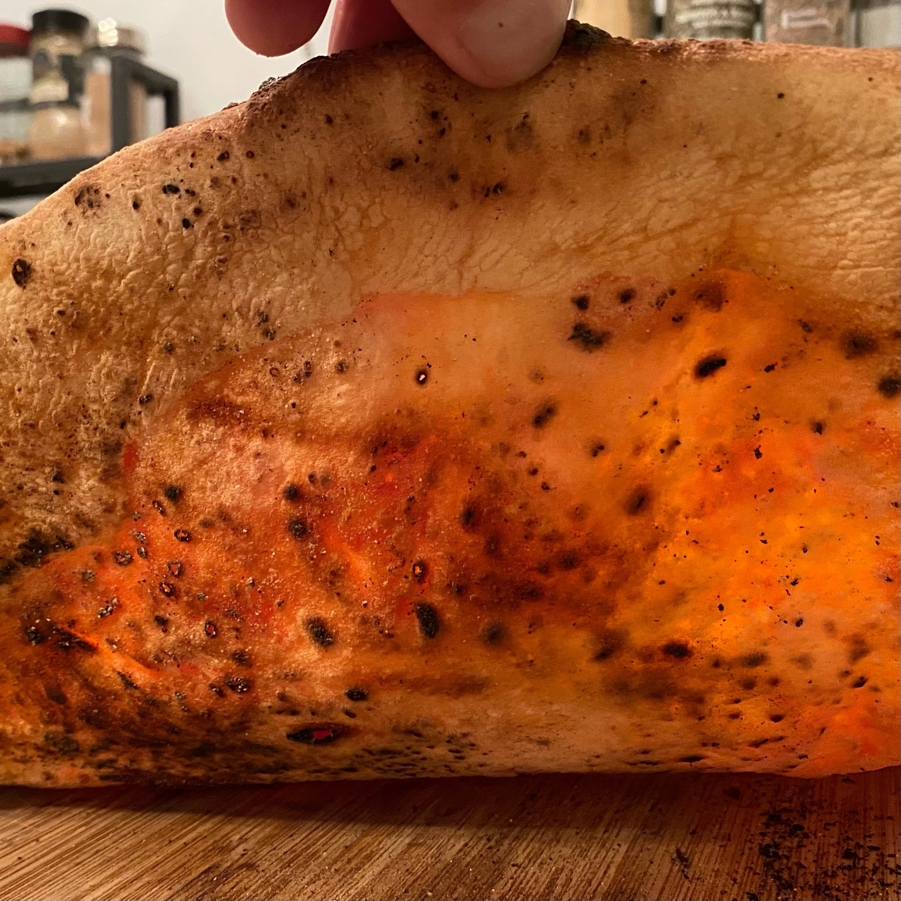 picture of a bottom of a cooked pizza with light shining through a thin crust