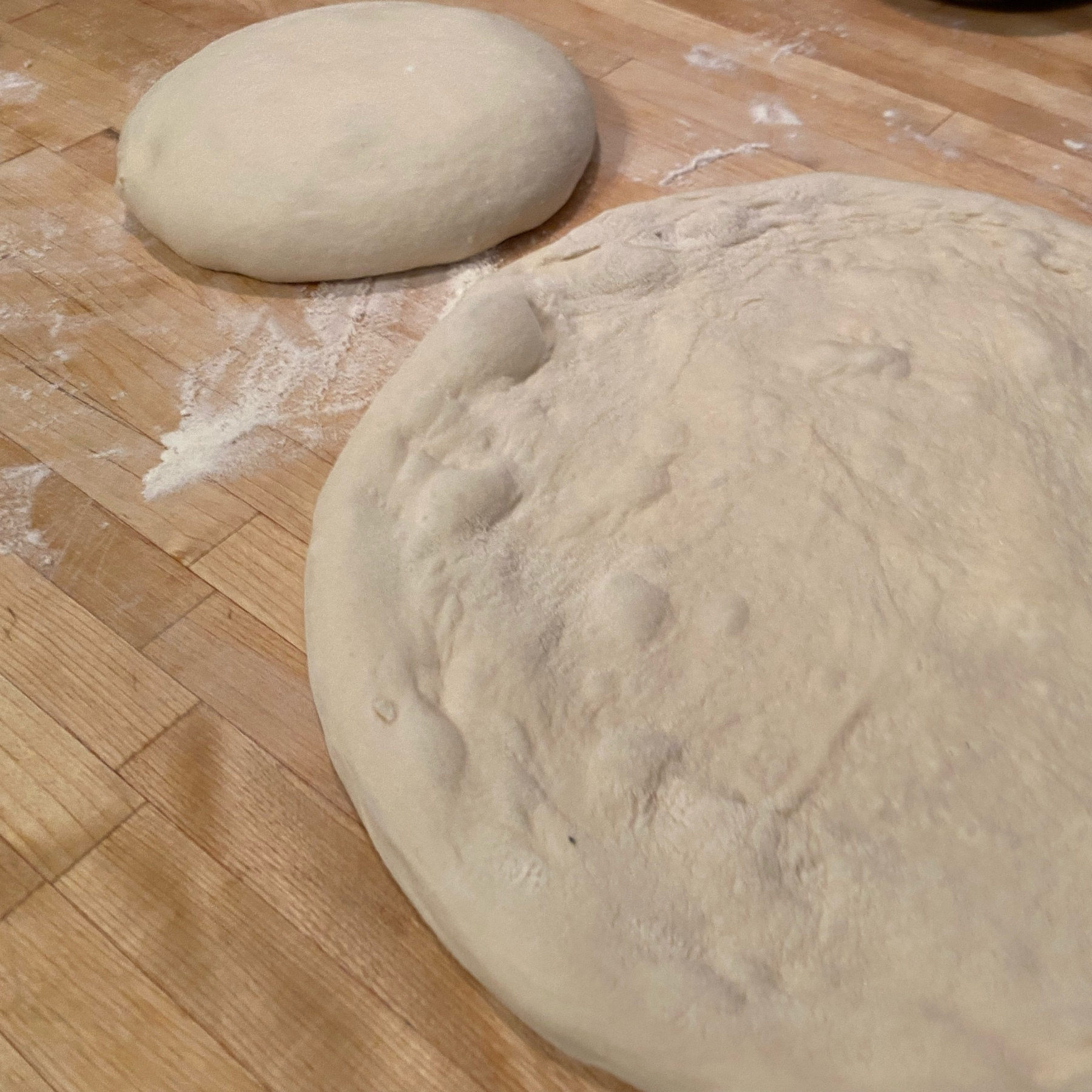 two dough balls, one stretched into a pizza shape and one in a round mound
